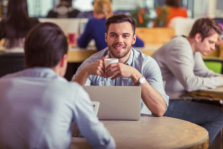 freelancers: Handsome young man is having a coffee break while working with other freelancers at the coffee shop Stock Photo