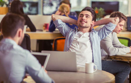 freelancers: Attractive young man is having a break while working with other freelancers at the modern office Stock Photo