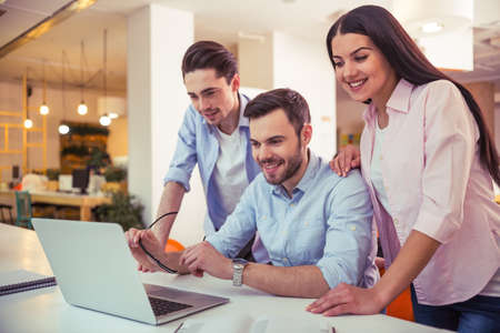 freelancers: Young freelancers are using a laptop, talking and smiling while working at the modern office