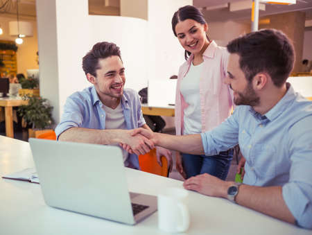 freelancers: Young freelancers are using gadgets, talking and smiling while working at the modern office. Men are handshaking