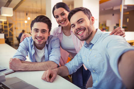 freelancers: Young freelancers are posing, looking at camera and smiling while working at the modern office