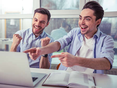 manager team: Happy young freelancers are using a laptop while working at the modern office Stock Photo