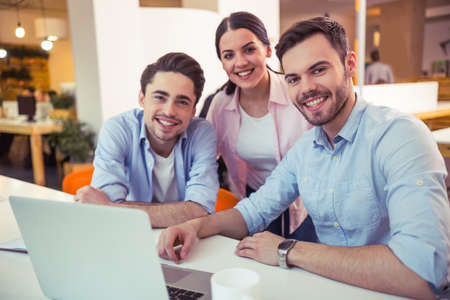 Young freelancers are looking at camera and smiling while working at the modern office