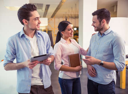 freelancers: Young freelancers are using gadgets, talking and smiling while standing at the modern office