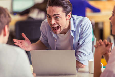freelancers: Irritated young man is using a laptop and screaming while working with other freelancers in cafe Stock Photo
