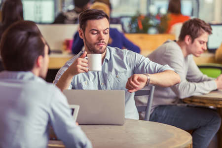 freelancers: Handsome young man is having a coffee break and looking at the watch while working with other freelancers at the coffee shop Stock Photo