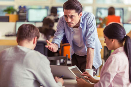 freelancers: Young freelancers are using gadgets and discussing affairs while working in office Stock Photo