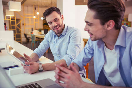 freelancers: Handsome young freelancers are using gadgets, talking and smiling while working at the modern office