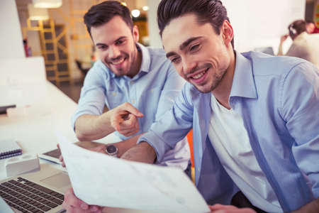 freelancers: Handsome young freelancers are discussing documents and smiling while working at the modern office Stock Photo