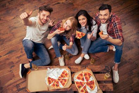 Hoogste mening van jonge mensen in vrijetijdskleding die pizza eten, en camera drinken drinken. Eén persoon vertoont het OK-teken