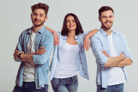 looking at camera: Beautiful young people in jeans are looking at camera and smiling, on a gray background. Woman is leaning on men