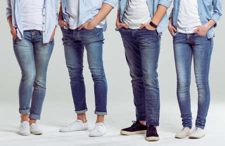 ジーンズの足のクローズ アップ、灰色の背景の上に立っての若者たち