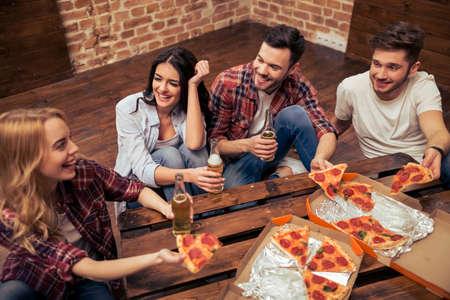 Junge Menschen in Freizeitkleidung, die Pizza essen, reden, lachen und trinken während des Ausruhens