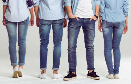 Young people in jeans standing on a gray background turned back except one man, legs close-up