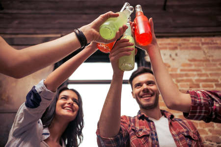 alcohol drinks: Young people in casual clothes are resting, clanging bottles of drink together and smiling, close-up Stock Photo