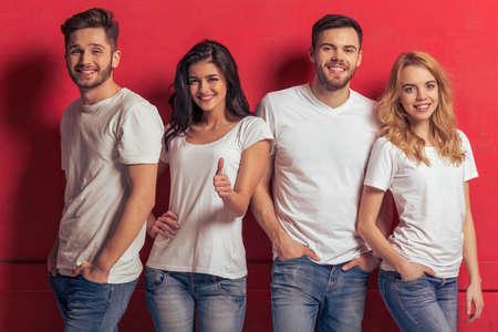 白い t シャツとジーンズの若者たちは、カメラと笑顔、赤い背景に立って見ています。女の子が Ok のサインを見せています。
