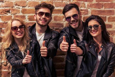 modelos posando: Dos hermosas parejas jóvenes con chaquetas de cuero y gafas de sol están mirando a la cámara, que muestra la muestra aceptable y que sonríe, contra la pared de ladrillo