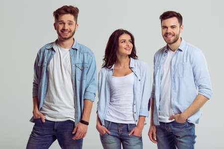 ropa casual: Beautiful young people in jeans are looking at camera and smiling, keeping hands in pockets, on a gray background