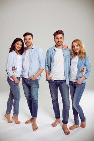 barefoot: Two beautiful young couples in jeans are looking at camera and smiling, standing barefoot on a gray background Stock Photo