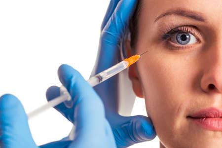 De vrouw bekijkt camera, de chirurg in blauwe medische die handschoenen maakt een injectie in gezicht, op een witte achtergrond, close-up wordt geïsoleerd