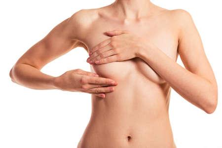 pechos: Hermosa mujer joven desnuda que cubre su pecho, aislada sobre un fondo blanco, primer plano