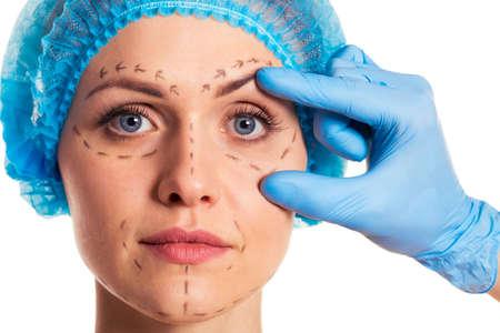 Schöne Frau in der medizinischen Kopfbedeckungen mit Skizzen auf Gesicht, Chirurg in medizinischen Handschuhen prüft ihr Gesicht, isoliert auf einem weißen Hintergrund