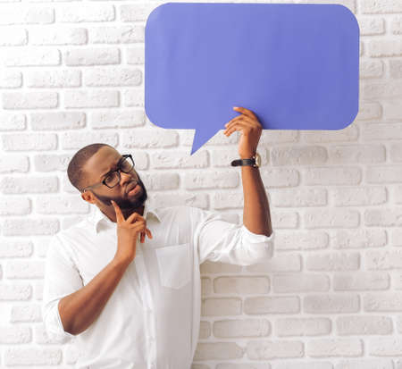 Handsome Afro American man in classic shirt and glasses is holding a speech bubble and thinking, standing against brick wall