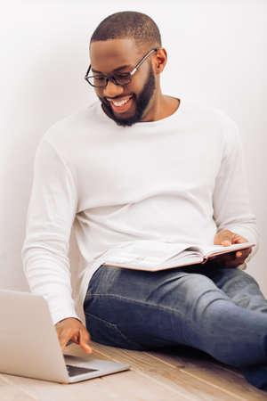 african man: Handsome Afro American man in glasses is making notes, using a laptop and smiling while sitting on the floor at home