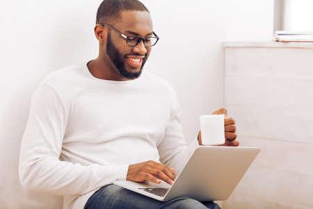 L'uomo afroamericano bello in vetri sta utilizzando un computer portatile, sta tenendo una tazza e sta sorridendo mentre lavorava a casa