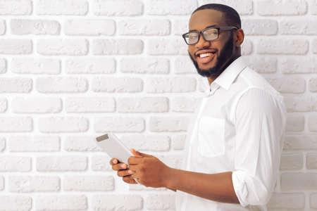 Vista lateral del hombre afroamericano en camisa clásica y gafas utilizando una tableta, mirando la cámara y sonriente, de pie contra la pared de ladrillo blanco