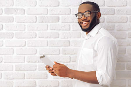Side view of Afro American man in classic shirt and glasses using a tablet, looking at camera and smiling, standing against white brick wall Stockfoto