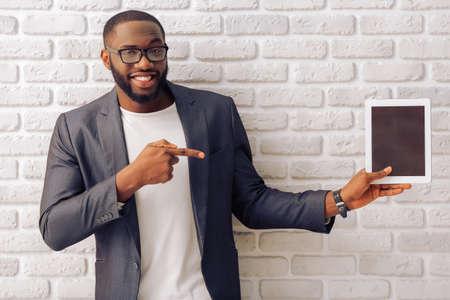 Knappe Afro-Amerikaanse zakenman in grijze klassieke jas en een bril is het presenteren van een tablet en glimlachen, staande tegen bakstenen muur Stockfoto