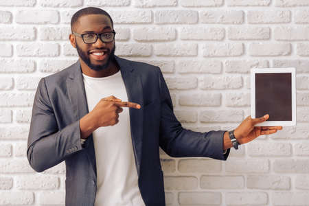 Handsome Afro American businessman in gray classic jacket and glasses is presenting a tablet and smiling, standing against brick wall Archivio Fotografico