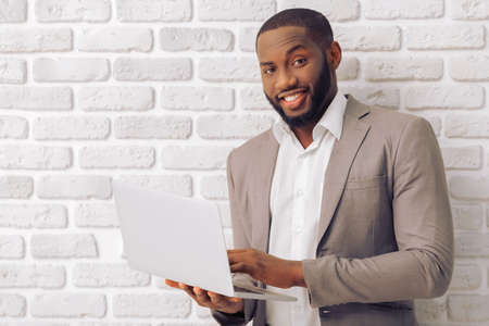 Handsome Afro American man in classic suit is using a laptop, looking at camera and smiling, against white brick wall