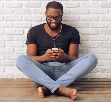 people listening: Handsome Afro American man in casual clothes and glasses is listening to music using a smart phone and smiling, sitting against white brick wall Stock Photo