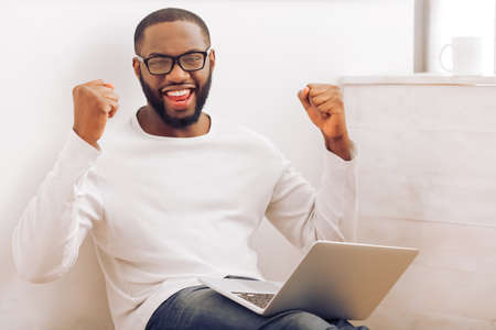 home keeping: Happy handsome Afro American man in glasses is using a laptop, keeping hands in fists and smiling while working at home