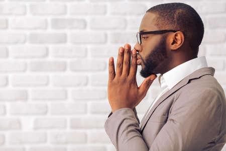 Vista laterale di uomo bello afro americano in vestito classico e bicchieri mantenendo palmi delle mani come in preghiera, in piedi contro il muro di mattoni bianco