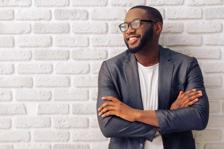 Handsome Afro American businessman in gray classic jacket and glasses is smiling, standing with crossed arms against brick wall Reklamní fotografie