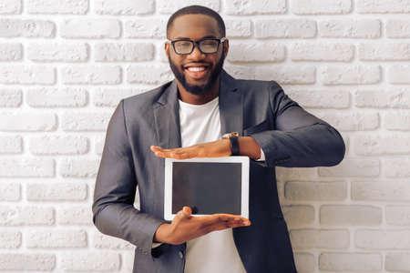 Apuesto hombre de negocios afroamericana en la chaqueta clásica gris y gafas está mostrando una tableta y sonriente, de pie contra la pared de ladrillo