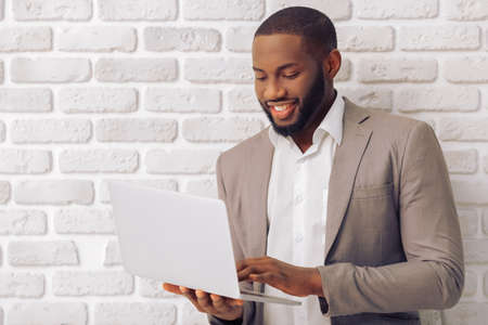 Handsome Afro American man in classic suit is using a laptop and smiling, against white brick wall