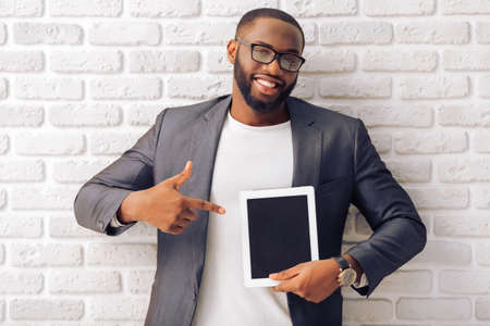 afro man: Handsome Afro American businessman in gray classic jacket and glasses is presenting a tablet and smiling, standing against brick wall Stock Photo