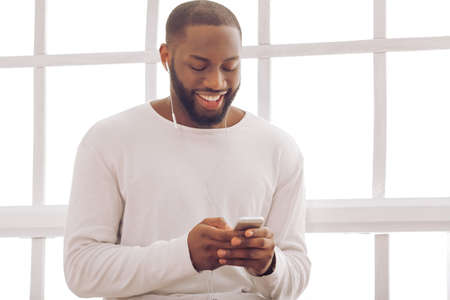 hombres de negro: Apuesto hombre afroamericano está escuchando la música usando un teléfono inteligente y sonriendo mientras está sentado cerca de la ventana en el país