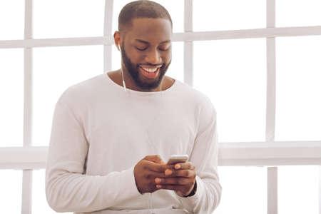 Knappe Afro-Amerikaanse man luistert naar muziek met behulp van een slimme telefoon en lachend zittend in de buurt van het raam thuis