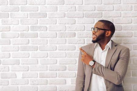 Uomo bello afro americano in vestito classico e bicchieri sorride, guardando e in direzione opposta, contro il muro di mattoni bianchi
