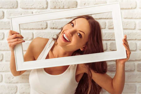 Beautiful young woman is holding a wooden frame, looking at camera and smiling, against white brick wall Stock Photo