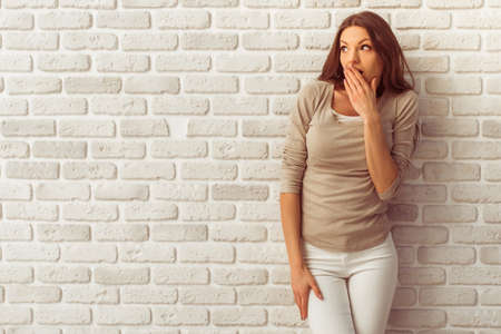 adult oops: Beautiful young woman in casual clothes is covering her mouth with surprise and looking away, against white brick wall