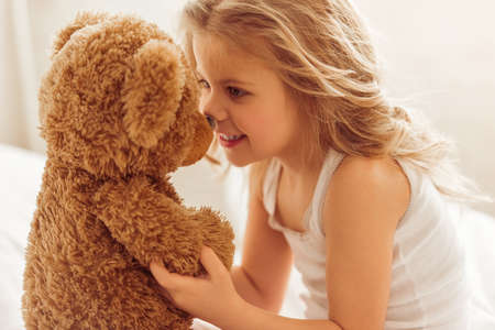 cute teddy bear: Sweet little girl is playing with a teddy bear and smiling while sitting on her bed at home