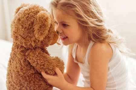 Dolce bambina sta giocando con un orsacchiotto e sorridente mentre seduto sul suo letto a casa