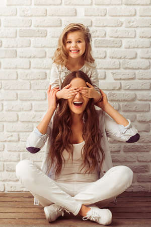 person sitting: Young mother and her little daughter are looking at camera and smiling, sitting against white brick wall. Girl is closing her mother eyes
