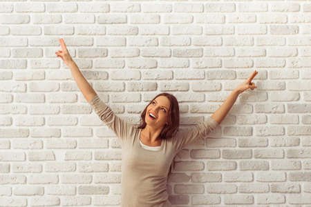 Happy beautiful young woman in casual clothes is pointing up and looking away, against white brick wall Reklamní fotografie